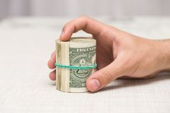 A man holds a bundle of money in his hand tied with an elastic band Royalty Free Stock Images