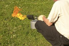 A man holds a burning soldering lamp in his hands stock photo