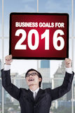 Man holds business goals for 2016. Young chinese businessman standing in the office while holding a board with a text of business goals for 2016 Royalty Free Stock Image