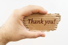 A man holds a cardboard in his hand on which it is written - Thank you