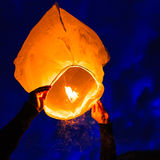 Man holds a chinese lantern as it begins to float Royalty Free Stock Photos