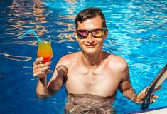 Man holds a cocktail in the swimming pool. Young handsome man holds a cocktail in the swimming pool Royalty Free Stock Images
