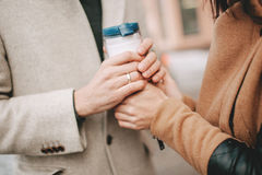 Man holds a coffee cup and woman hands in winter Stock Images