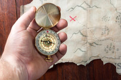 Man holds compass above fake pirate map of abstract island with red cross of place where is treasure Stock Photo