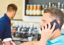 Man holds cup of drink while have mobile conversation. Coffee to go useful option for busy people. Call friend to have royalty free stock photography