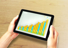 Man holds digital tablet with business chart on a screen Royalty Free Stock Images