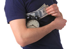Time is money. Man holds dollars and an alarm clock Stock Image