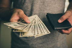 A man holds dollars and black wallet in his hands Royalty Free Stock Image