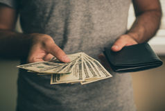 A man holds dollars and black wallet in his hands Stock Image