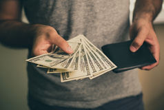 A man holds dollars and black wallet in his hands Stock Photography