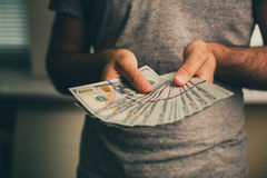 A man holds dollars in his hands Stock Photos