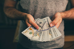A man holds dollars in his hands Royalty Free Stock Photos