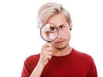 Man holds on eye magnifying glass looking through loupe Royalty Free Stock Image