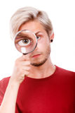 Man holds on eye magnifying glass looking through loupe Stock Photo