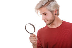 Man holds on eye magnifying glass looking through loupe Stock Images