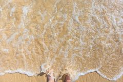 Man holds feet in the surf of a sand beach royalty free stock photos