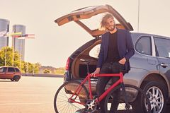 A man holds fixed bicycle near the car with open trunk. royalty free stock photo