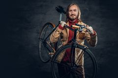 A man holds fixed bike. Stylish bearded male with long hair holds fixed bicycle on a shoulder in a studio royalty free stock photography