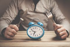 Man holds fork with knife. Time to eat. Stock Image