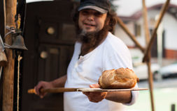 Man holds freshly baked bread. Man with a beard holds freshly baked bread royalty free stock image