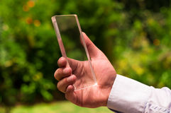 Man holds futuristic transparent smart phone in a green blurred background.  Stock Photos