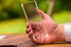 Man holds futuristic transparent smart phone in his hand.  Royalty Free Stock Photography