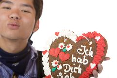 Man holds gingerbread heart and give kiss Royalty Free Stock Photography
