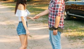 A man holds a girl by the hand, talks, offers marriage.in the background is a black car.offering.girl pulls out her hand, wants to royalty free stock image