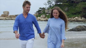 The man holds the girl by the hand. They walk along the beach, talk and smile stock video