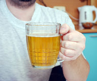 The man holds a glass of beer in hand Royalty Free Stock Images