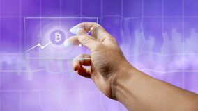 A man holds a glass screen with a bitcoin symbol and a crypto currency graph. A businessman holds a glass screen with a bitcoin symbol and a crypto currency stock images
