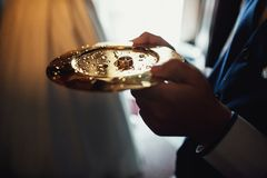 Man holds golden plate with wedding rings in church. Original wedding rings lie on the steel plate on a table in church Stock Images