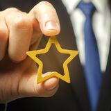 Man holds a golden star in his hand. Symbol of success and excellence. Good reputation, prestige, high recognition. Status, rating