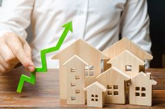 A man holds a green arrow up near a set of houses or a city. Growth indicators of the city, raising the attractiveness, safety. And prosperity of the city stock photos