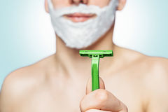 Man holds green razor Stock Photography
