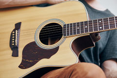 A man holds a guitar, musical instruments, music, strings, a mediator.  Stock Images