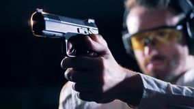 Male shooter holds a gun in a shooting room, close up. A man holds a gun and aims at a target stock video footage