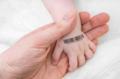 Man holds hand of a baby with bar code on it. Genetic cloning concept royalty free stock images