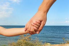 Man holds hand of child on background of sea and sky. Stock Image