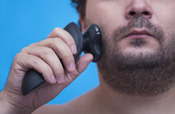 Shaving man. The man holds in a hand the electric razor at a cheek, a half of the face Royalty Free Stock Photography