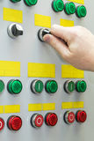 A man holds the hand of the head switch of the electric Cabinet. On the door of the electric Cabinet are indicator lamp and head of mechanical switches Stock Photography