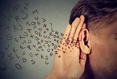 Man holds hand near ear listens carefully alphabet letters flying in Stock Photo