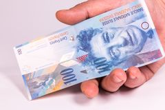 A man holds in his hand a Swiss banknote close-up stock photography
