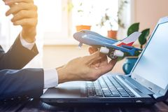 Man holds in hand toy airplane. The concept of travel, booking and purchase tickets online Stock Image