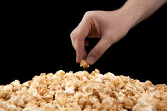 Man holds a handful of popcorn in his hand. On a black background royalty free stock image