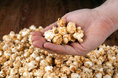 Man holds a handful of popcorn in his hands. Close up royalty free stock photo