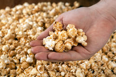 Man holds a handful of popcorn in his hands Stock Photos
