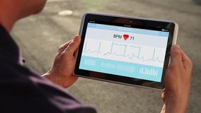 Man Holds Tablet Device to Monitor His EKG. A man holds a handheld device or tablet PC that monitors and records his heartbeat and EKG. EKG and screen animation stock video