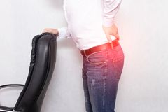 A man holds his back holding an office chair concept of back pain, pinched nerve and myofascial syndrome, inflammation, lumbago. A man holds his back holding an stock photography