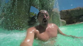 Man holds his breath and dives under the water. In the pool stock footage